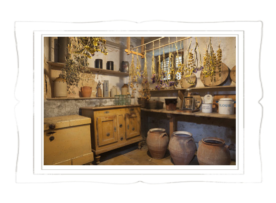 The Game Larder with hanging bunches of dried herbs and flowers, wooden storage chests and earthenware urns at Gunby Hall, Lincolnshire © National Trust